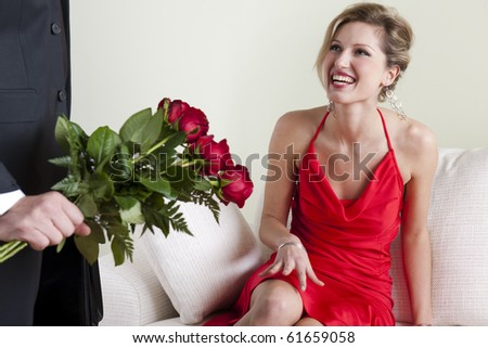 Happy beautiful woman receiving red roses on Valentine's Day, Birthday or Wedding Anniversary