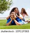 Happy beautiful young family lying on the green grass. Three cheerful person - stock photo