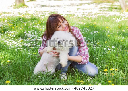 Happy beautiful young woman, enjoying nature with her dog, at sunny spring day in the park.