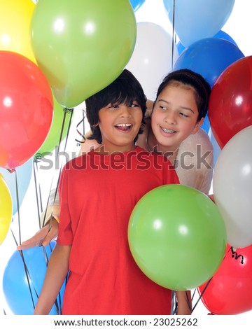 Happy biracial siblings surrounded by helium balloons.