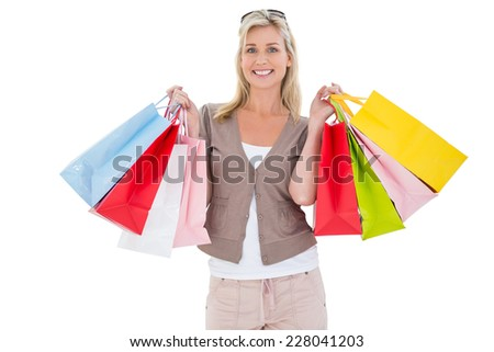 Happy blonde holding shopping bags on white background