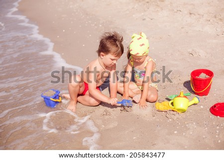 happy boy and girl playing in the sand on the seashore