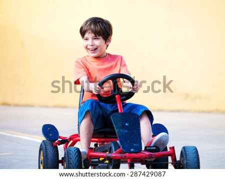 Happy boy child riding a pedal cart