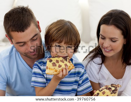 Happy boy eating pizza with ihs parents in living-room
