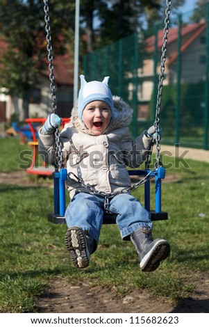 Happy Boy Playing On A Swing
