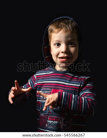 Happy boy with hoodie standing over black background