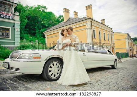 happy bride and groom on the background of a limo