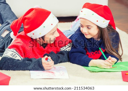 Happy brother and sister laying and writing with Christmas hat.