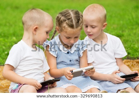 Happy brothers and sister using smartphones sitting on the grass