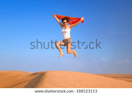 Happy brunette jumping in the desert