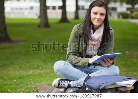 Happy brunette student using tablet sitting on bench on campus at college