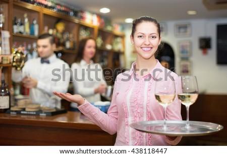 Happy brunette waitress and barmen working in modern bar
