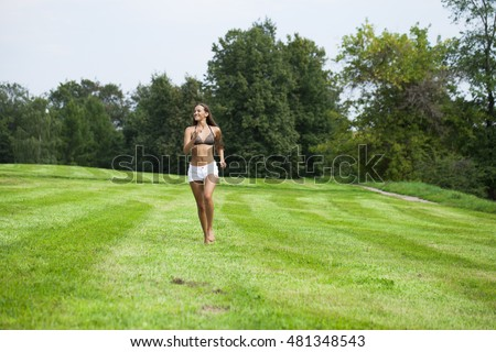 Happy brunette Woman running on summer or spring grass field