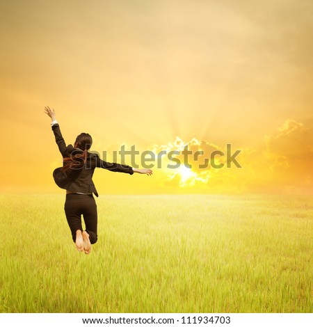 Happy Business woman jumping to sunset in grassland