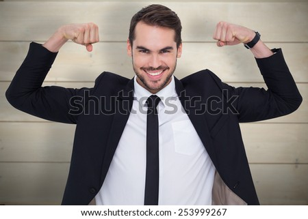 Happy businessman in suit cheering against bleached wooden planks background