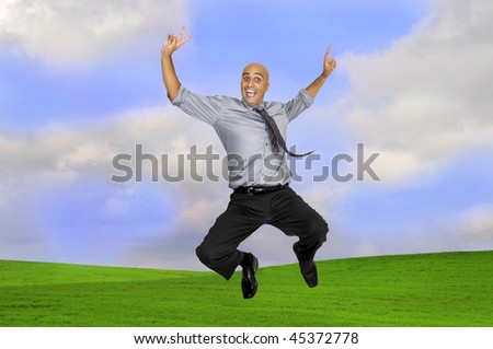 Happy businessman jumping outdoors in a green field