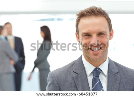 Happy businessman posing in front of his team while working on the background