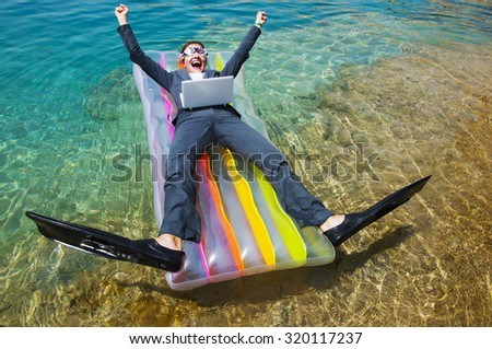 Happy businesswoman in goggles and flippers with laptop on floating mattress. Travel concept