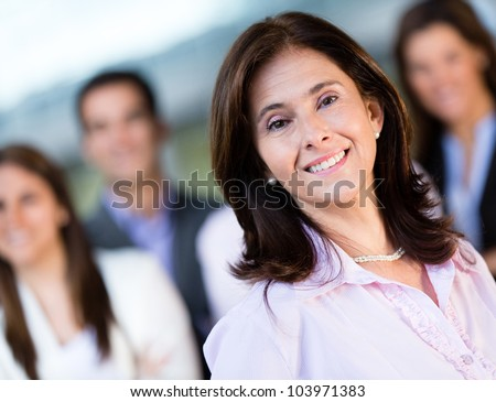 Happy businesswoman with a group smiling at the office