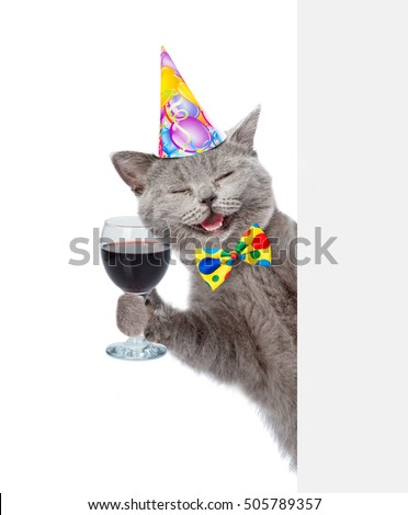 Happy cat in birthday hat holding wineglass. isolated on white background