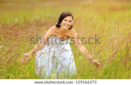 Happy caucasian bride at field laughing.