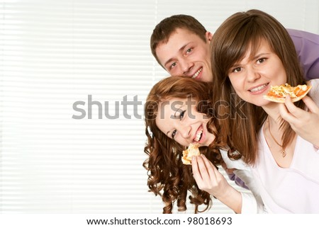 Happy Caucasian campaign of three people eating pizza on a light background