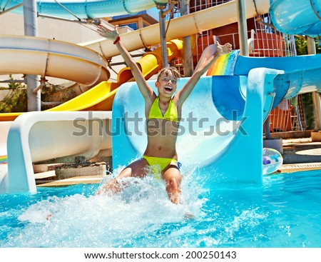 Happy child girl in bikini sliding water park.
