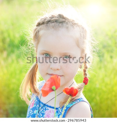 Happy Child Girl in Summer Sunny Park. Beautiful Red Hair Girl with Flowers in Sun Rays.