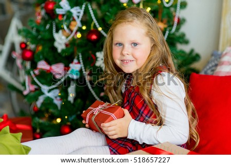 happy child girl with elf boots near a decorated Christmas tree surprized by Christmas gifts