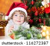 Happy child in Santa hat against Christmas tree with decorations - stock photo