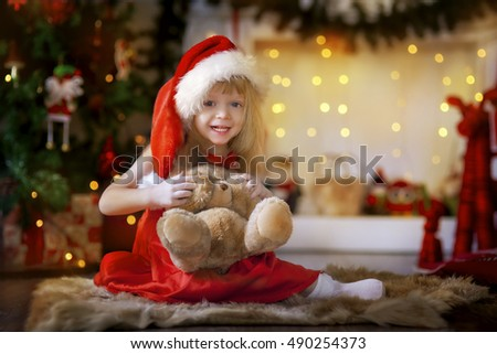 Happy child in Santa hat with teddy bear
