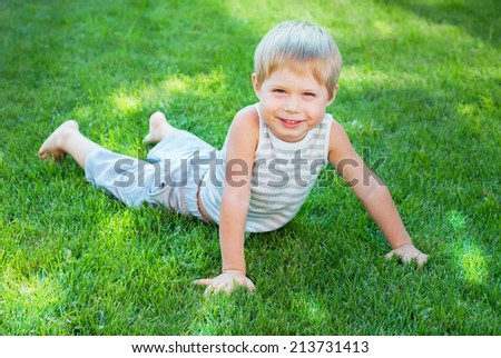 Happy Child Laying on a Green Grass in Sun Light