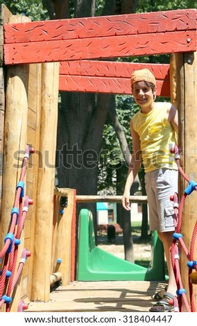happy child plays in the outdoor playground in the summer