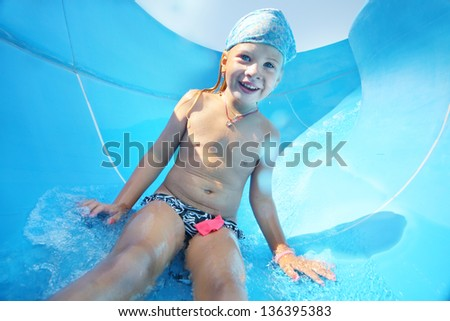 Happy child rolling from slide in water park at sunny summer day.