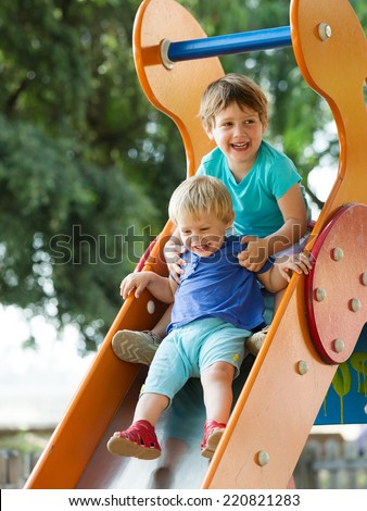 happy children on slide at playground area