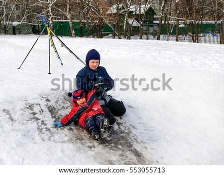 Happy children sliding from a little snowy hill. Child at winter
