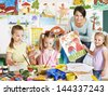 Happy children  with teacher at school. - stock photo