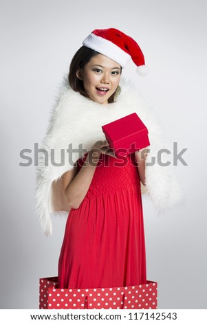 Happy Chinese girl jumping out of a bag wearing a santa hat
