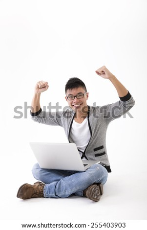 Happy Chinese man using a laptop PC and cheering. Isolated on White Background.