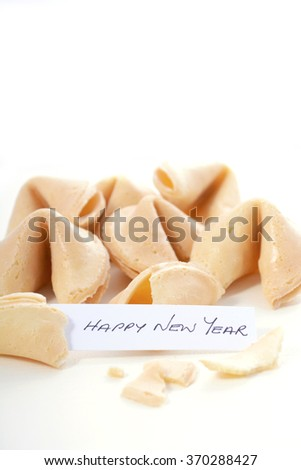 Happy Chinese New Year message inside closeup of fortune cookies on a white wood table, vertical with copy space.