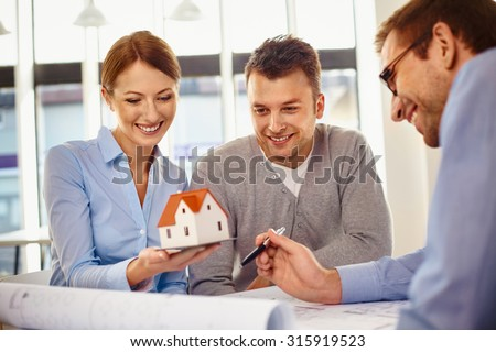 Happy couple choosing new home design with architect