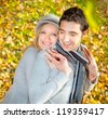 Happy couple have a romance in fall  branches of wood - stock photo