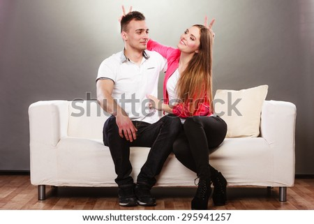 Happy couple having fun and fooling around. Joyful man and woman have nice time using fingers as bunny ears. Good relationship.