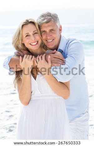 Happy couple hugging each other by the sea at the beach