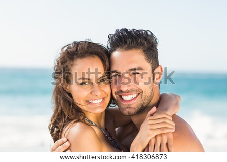 Happy couple hugging on the beach on a sunny day
