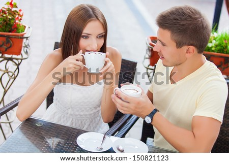 Happy couple in love drinking coffee and looking at each other