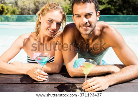Happy couple leaning on pool edge and holding cocktails in a sunny day