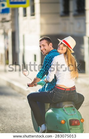 Happy couple on a scooter outdoors