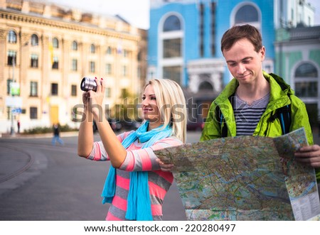 Happy couple on travel vacation holidays. Young beautiful woman taking photo, young man looking to map