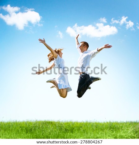 Happy Couple Outdoor. Jumping Family on Green Field. Freedom concept. Free. Jumping People. Fun